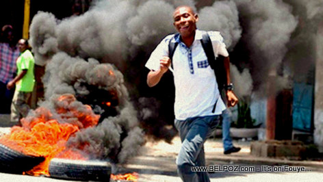 Haitian student running by burning tires amid protests