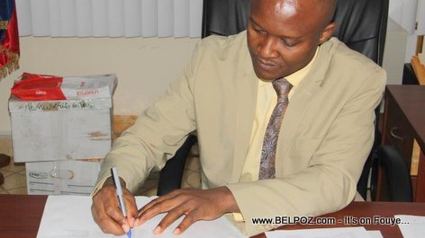 Haiti Education DG Meniol Jeune signing deal to build 12 new schools