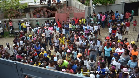 A large crowd of Haitian parents and students gather to collect free school bags