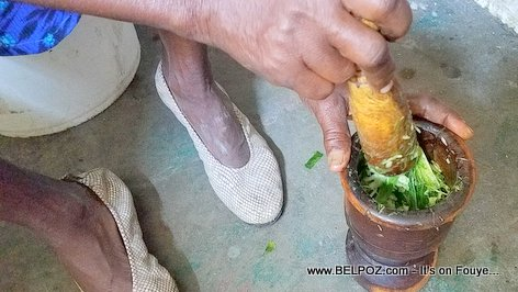 Cooking: A Haitian woman mashing up poireau (leek), with garlic and other spices in her pilon