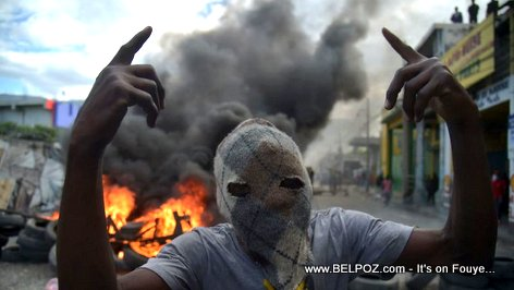 PHOTO: Haitian Street Protester with baricade of fire behind him