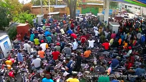 Scene of Motorcycles piled up at a gas station in Haiti looking waiting for fuel