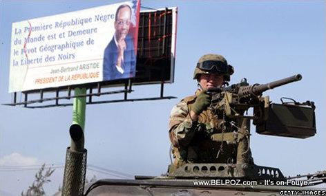 PHOTO: Haiti - Yon Solda Americain zam a la main devan yon poster President Aristide