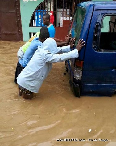 PHOTO: Flooding in Cap Haitien Haiti - Residents trying to push a vehicle out of the flood water