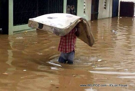 PHOTO: Cap Haitien Haiti Flooded, one man tries to save his belongings